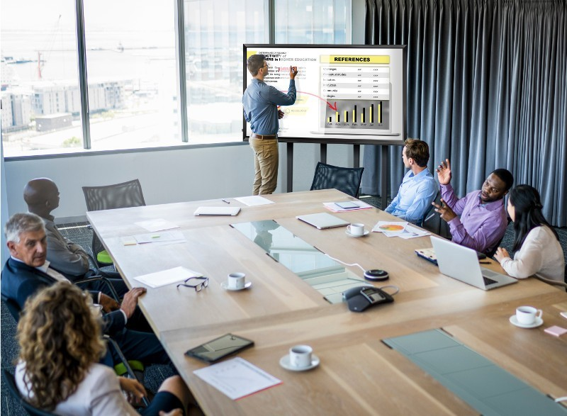 Businessman giving presentation to colleagues. Male and female professionals are planning in meeting. They are sitting at conference table in office.