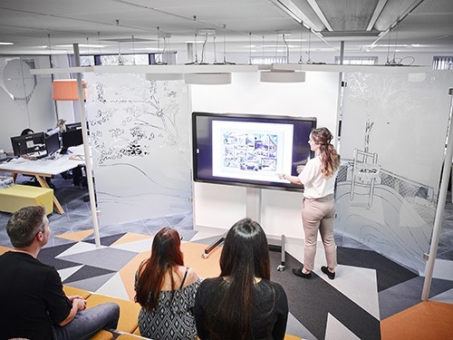 Woman using Clevertouch to present drawings to a group