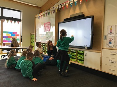 K12 child using Clevertouch interactive display in the classroom while classmates watch