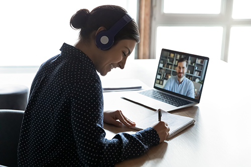 Smiling young indian woman in headphones learning practicing foreign language with confident male tutor distantly on computer. Happy mixed race girl listening to educational webinar, writing notes.